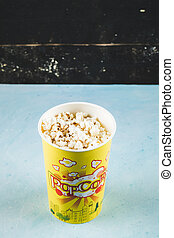 Popcorns in a yellow box on black background