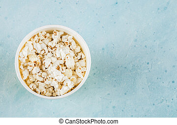 Popcorns in a yellow box on blue table, top view