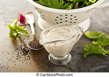 Poppy seed salad dressing or sauce in a glass dish with...