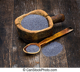 poppy seeds in a wooden bowl on a background of the old wooden table
