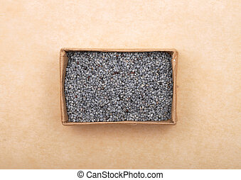 Poppy seeds in carton on brown background