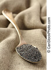 Poppy seeds in metal spoon on sackcloth background