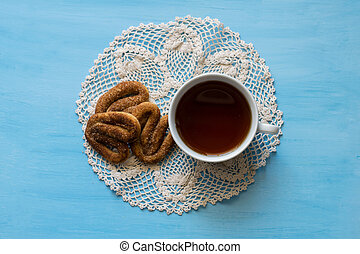 Poppy with pretzels on a blue board with a cup of tea. A cup of tea and pretzels with cinnamon.