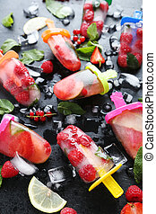 Popsicles with berries on black wooden table