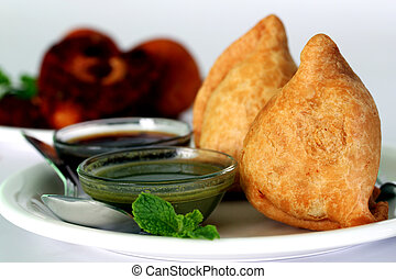Popular indian, asian and african deep fried snack called samosa with spicy chutney and mint