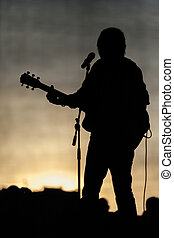 Popular music concert equipment on stage and musician silhouette