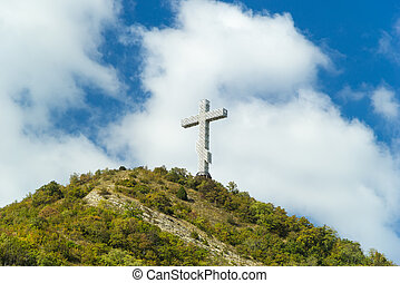 Popular sight of the Gelendzhik resort city. Worship cross on hill of Caucasian mountain against blue cloudy sky background.