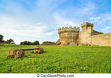 Populonia medieval village landmark, bench, city walls and tower. Tuscany, Italy.