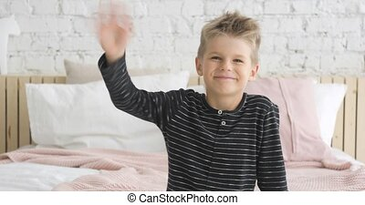 Poratrait of smiling little boy of 5 ages looking at camera and waving hand.
