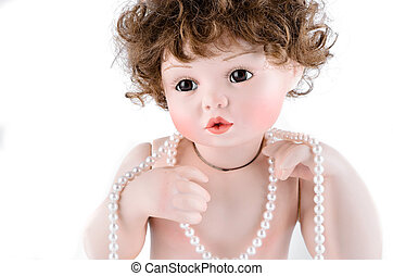 Porcelain doll with pearl beads closeup on white background
