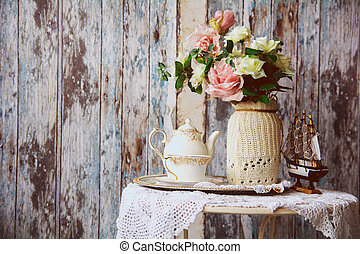 Porcelain teapot and cup on a table with a vase with artificial