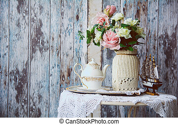 Porcelain teapot and cup on a table with a vase with...