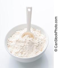 porcelain white bowl with spoon full of flour