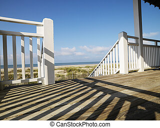 View of beach from porch with railing casting shadow on wooden deck at Bald Head Island, North Carolina