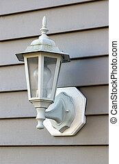 Porch Light - A porch light against a brown vinyl siding