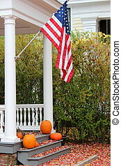 Porch steps with flag and pumpkins