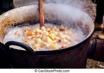 Traditional way of melting fresh pork fats, bacon, making crackling in deep iron cauldron.