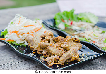 pork chitterlings fried served with fresh vegetable on dish