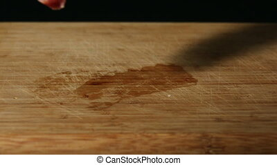 Pork chop falling onto wooden table in slow motion