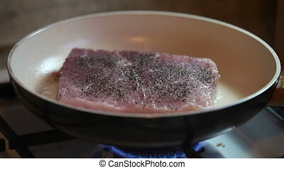 Pork chop frying on the pan