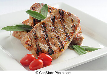 Juicy pork chop grilled and garnished with sage.