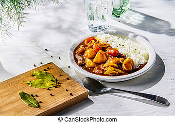 Pork curry with white rice on plate.