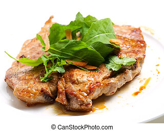 Pork cutlet or chop is decorated with salad.