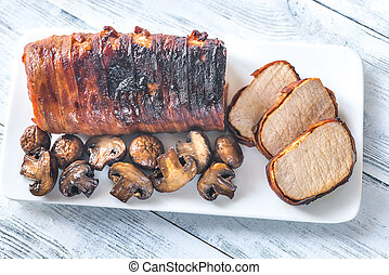 Pork loin wrapped in bacon with roasted mushrooms