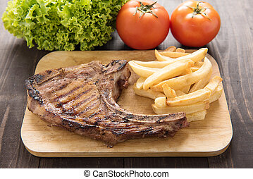 Pork meat grilled with french fries and vegetables on wooden background.