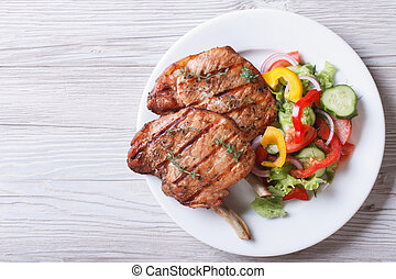 Pork meat grilled with fresh vegetable salad top view - Pork...