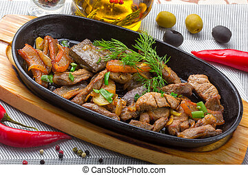 Pork meat grilled with fresh vegetable salad on a plate with garnish and spices