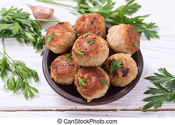 Pork meatballs with parsley in bowl .