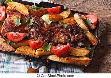 pork ribs, potatoes and tomatoes closeup. Horizontal top view