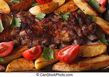 pork ribs, potatoes and tomatoes macro. horizontal top view
