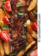 pork ribs, potatoes and tomatoes macro. Vertical top view