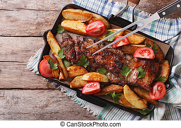 Pork ribs with baked potatoes in a pan closeup. horizontal top view