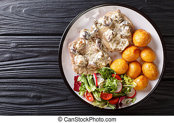 Pork steak in creamy mushroom sauce with a side dish of fresh potatoes and vegetable salad close-up. Horizontal top view