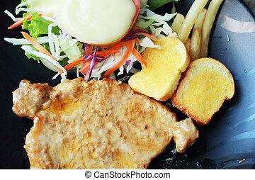 Pork steak with vegetable salad on plate.