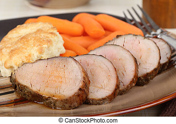 Pork Tenderloin Dinner - Sliced pork tenderloin on a dinner...