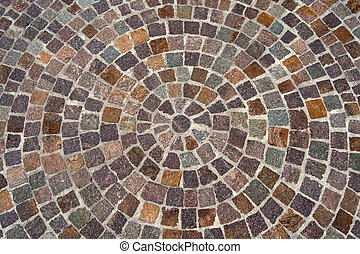 Geometric floor with multi colored blocks of porphyry (sanpietrini), typical urban paving in Italy