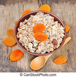 Porridge with apricots on wooden background. Home cuisine. ...
