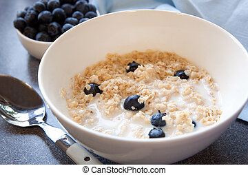 Bowl of oatmeal with fresh blueberries. Traditional Scottish oatmeal, healthy and delicious.