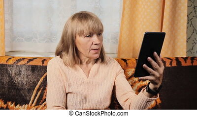 Porrtait of senior woman using electronic tablet at home for video calling