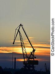 Port cargo crane over sunset sky background