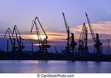 Port cargo crane over sunset sky background