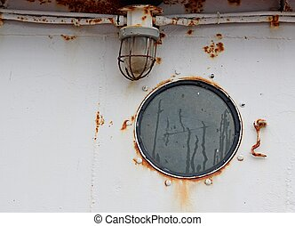 Port hole window and exterior light on a rusty old ship in the harbor