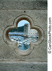 view on the port in Dubrovnik from the hole in bridge - the wall is sharp and the port is blurred