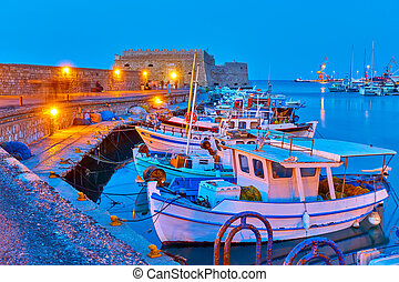 Port of Heraklion with old fishing boats at twilight Crete, ...