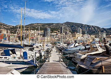 Port in Monaco principality, pier with yachts and sailing boats, view to Monte Carlo, Mediterranean Sea coast.
