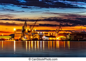 Sunset over an industry harbor with cranes in Stavanger, Norway.